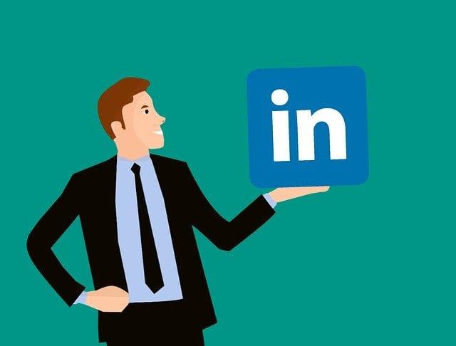 Businessman holding a LinkedIn logo.