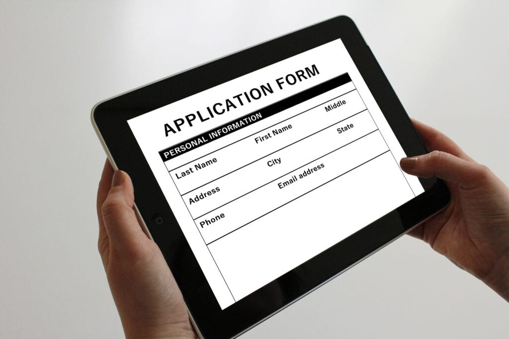 Image shows a job application displayed on tablet being held in someone's hand.