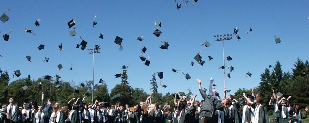Class throwing diplomas in the air
